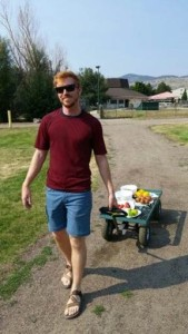 A man pulling a garden wagon with fruits